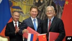 Presiden Rusia Vladimir Putin (kiri), CEO perusahaan gas Rusia Gazprom Alexei Miller (tengah) dan pimpinan perusahaan minyak China (CNPC) Zhou Jiping seusai penandatanganan perjanjian gas antara kedua negara di Shanghai, China (21/5).