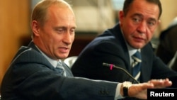 FILE - Russian President Vladimir Putin (L) and Mikhail Lesin, Russian press minister at the time, are seen at a meeting in Vladivostok, Russia, Aug. 24, 2002. Lesin, once considered a Putin associate, was found dead with blunt-force injuries in a Washington hotel room last November.
