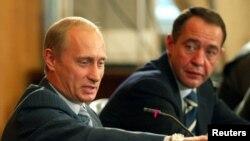El presidente ruso Vladimir Putin y su vocero Mikhail Lesin, durante una reunión en Vladivostok, Russia, el 24 de agosto de 2002.