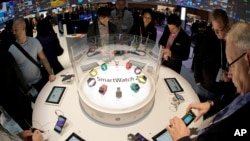 FILE - Trade show attendees examine the Sony Smart Watch 2 on display at the International Consumer Electronics Show, Jan. 8, 2014, in Las Vegas. High-tech tools can be used to help students cheat on exams, experts say.