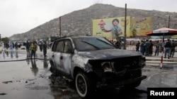 Seorang petugas pemadam kebakaran Afghanistan memeriksa kendaraan yang hangus setelah berupaya memadamkan api yang membakar mobil tersebut di Kabul (16/8). Sedikitnya 17 orang dilaporkan tewas, Sabtu (17/8) akibat serangan militan di tiga lokasi terpisah di Afghanistan.