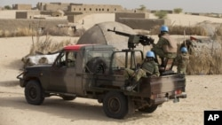 FILE - U.N. peacekeepers from Burkina Faso stand guard during a patrol through a neighborhood on the outskirts of Timbuktu, Mali.
