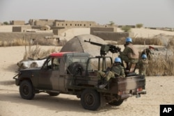 FILE - UN peacekeepers from Burkina Faso stand guard during a patrol through a neighborhood on the outskirts of Timbuktu, Mali, March 31, 2014.