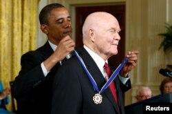 奥巴马总统在白宫把总统自由勋章授予前宇航员和参议员约翰·格伦。(2012年5月29日)