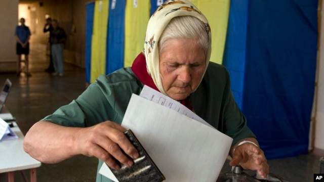 An elderly woman casts her vote in the presidential election in the eastern town of Krasnoarmeisk, Ukraine, May 25, 2014.