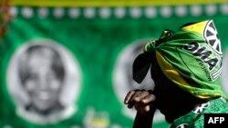 Yon dam -ki gen nan tèt li yon mouchwa ki senbolize Pati Kongrè Afriken an (African National Congress - ANC)- kanpe tou pre yon foto Nelson Mandela devan lopital kote ansyen lidè sid afriken an ye nan vil Pretoria (28 jen 2013).
