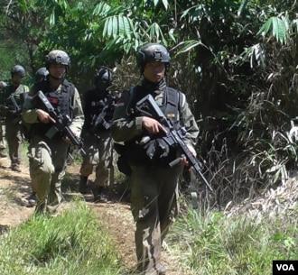 Pasukan Brimob berjalan kaki di hutan Desa Pantangolemba, Kabupaten Poso, Sulawesi Tengah. (VOA/Yoanes Litha)
