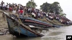 救援人員星期二在在印度東北部的布拉馬普特拉河中奮力把傾覆的渡輪拉上岸