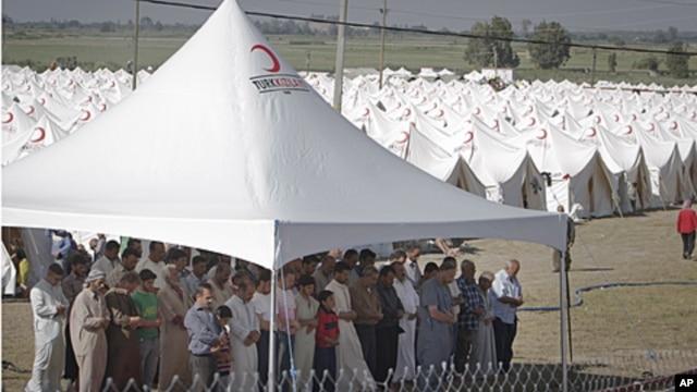 Syrian refugees pray in a camp in Boynuyogun, Turkey, near the Syrian border, June 16, 2011