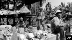 A Cambodian villager sits near human skulls recovered from debris in provincial Cambodia after government troops retook a village on Route 3, southwest of Phnom Penh in 1973. The skeletal remains were those of civilians and soldiers killed by Khmer communists.
