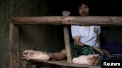 FILE - A man suffering from mental illness sits chained on a bed in his room inside his family home in Curug Sulanjana village in Serang, Banten province, Indonesia, March 23, 2016.