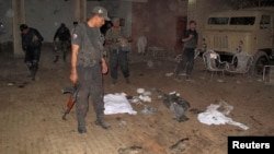 Security officials gather at the site of a suicide bomb blast in the outskirts of Dera Ismail Khan, Oct. 16, 2013.