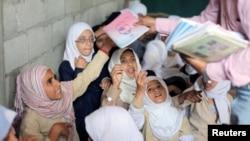 Para siswa menerima buku di rumah guru mereka yang diubah menjadi kelas untuk mendapatkan pendidikamn gratis di Taiz, Yaman, 18 Oktober 2018. (Foto: dok).