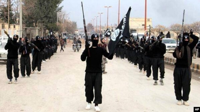 FILE - This undated file image posted on a militant website, Jan. 14, 2014, which has been verified and is consistent with other AP reporting, shows fighters from the al-Qaida linked Islamic State of Iraq and the Levant (ISIL) marching in Raqqa, Syria. (AP Photo/Militant Website)