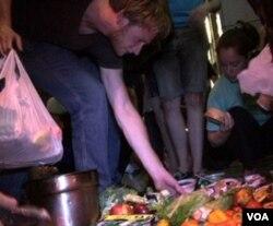 Buah, sayur segar, keju dan yogurt dikumpulkan dari tempat sampah di trotoar depan sebuah supermarket.