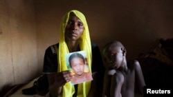 Rachel Daniel, 35, holds up a picture of her abducted daughter Rose Daniel, 17, at her home in Maiduguri, Nigeria, May 21, 2014.