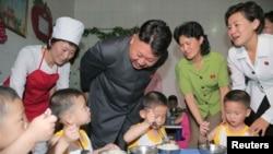 មេដឹកនាំកូរ៉េខាងជើង Kim Jong Un ញញឹមខណៈពេលដែលក្មេងៗញ៉ាំអាហារកំឡុងទស្សនៈកិច្ចនៅមណ្ឌលកុមារកំព្រាព្យុងយ៉ាងនៅទិវាកុមារអន្តរជាតិកាលពីថ្ងៃទី២ ខែមិថុនា ឆ្នាំ២០១៤។