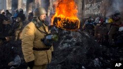 30일 우크라이나 수도 키에프에서 반정부 시위대가 경찰에 맞서 쌓아올린 타이어가 불에 타고 있다.
