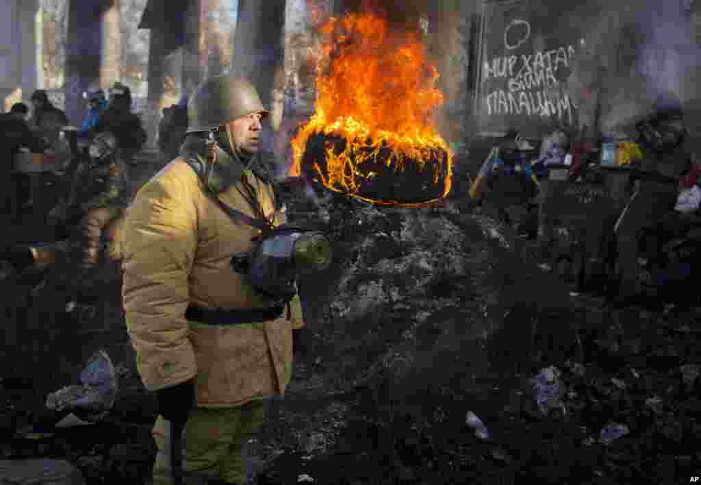 An opposition supporter stands next to a burning tire at a barricade in central Kyiv, Jan. 30, 2014.