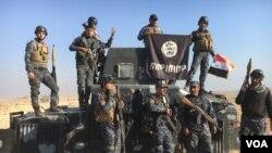 Les forces irakiennes célèbrent leur victoire sur les militants de l'Etat islamique avec le drapeau du groupe Etat islamique à Mossoul, Irak, 23 février 2017. (K. Omar / VOA)
