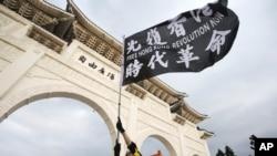 一名在台灣的香港人在台北自由廣場舉旗抗議中共在香港的暴政。(美聯社照片)