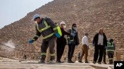 مصر میں بلدیہ کے اہلکار اہرام کے نزدیک جراثیم کش ادویات کا چھڑکاؤ کر رہے ہیں۔