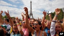 Children gesture during a live music concert of the Vacation for Everyone day event at the Eiffel Tower in Paris, France, Aug. 19, 2015.