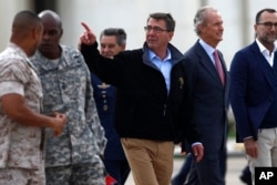 U.S. Secretary of Defense Ashton Carter, center, and Spain's Defense Minister Pedro Morenes, right, walk together during their visit at Moron Airbase, near Seville, Spain, Oct. 6, 2015.