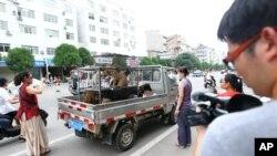 活动人士在玉林狗肉市场拦下一辆小卡车,谈判赎买价钱,以拯救即将被宰杀的狗。(2014年6月20日)