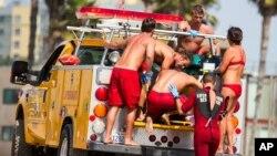 Salvavidas ayudan a una persona que estaba en el agua cuando cayó el rayo el domingo por la tarde en la playa de Venice, en Los Ángeles.