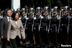 FILE - Taiwanese President Tsai Ing-wen inspects honour guard before a ceremony to mark the 92nd anniversary of the Whampoa Military Academy, in Kaohsiung, southern Taiwan, June 16, 2016.