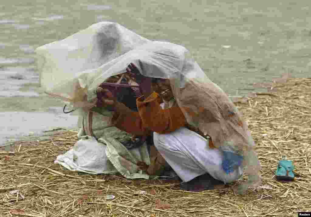 Những em gái dùng một tấm ni-lông để che mưa trên bờ sông Hằng ở thành phố Allahabad thuộc miền bắc Ấn Độ.