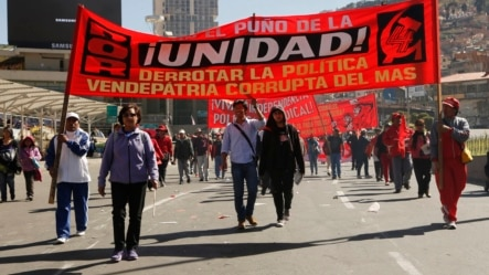 """Workers march in front of a banner with a message that reads in Spanish """"The fist of unity, defeating the traitorous policies of MAS (ruling party),"""" during a May Day march, in La Paz, Bolivia, May 1, 2015."""