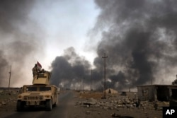 FILE - Iraqi security forces patrol as smoke rises from burning oil wells in Qayara, south of Mosul, Iraq, Aug. 31, 2016.