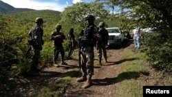 FILE - Soldiers guard an area where a mass grave was found, in Colonia las Parotas on the outskirts of Iguala, in Guerrero, Mexico.