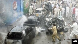 巴基斯坦南部城市奎達發生自殺炸彈手引爆汽車炸彈後消防員在現場向受損壞汽車噴灑水。