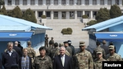 U.S. Secretary of State Rex Tillerson stands with U.S. Gen. Vincent K. Brooks (third from right) and Gen. Leem Ho-young (third from left), as North Korean soldiers look at the south side in the border village of Panmunjom, which has separated the two Koreas since the Korean War, March 17, 2017.