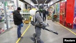 在俄羅斯首都莫斯科,一名身著防護裝備的人在噴灑消毒劑。(2020年4月9日)