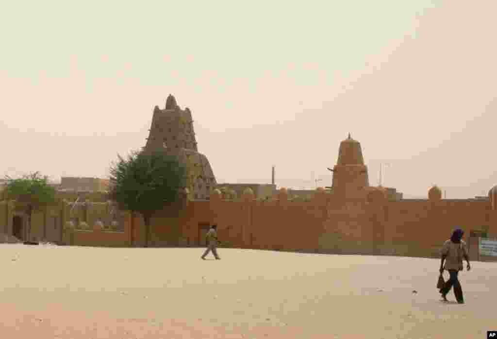 Cette photo d'avril 2012 montre des gens passant près de la mosquée Sankoré de Tombouctou, inscrite au patrimoine mondial de l'UNESCO.