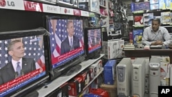 A Palestinian watches the speech of US President Barack Obama on television at a store in Gaza City, May 19, 2011