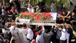 Bahraini mourners march in funeral procession in the western village of Karzakan, Bahrain, carrying the body of Isa Abdel Hasan, who died Thursday during clashes in Pearl Square in the capital of Manama, February 18, 2011