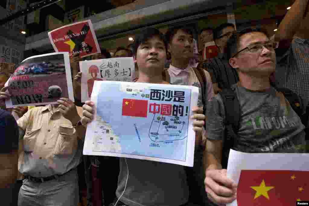 Anti-Vietnam protesters hold posters with slogans and a map of the South China Sea during a protest defending China's territorial claim and condemning Vietnam's anti-Chinese protests, in Hong Kong, May 19, 2014.