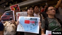 Anti-Vietnam protesters hold posters with slogans and a picture showing a map of the South China Sea, including the Paracel Islands, during a rally in Hong Kong defending China's territorial claims, May 19, 2014.