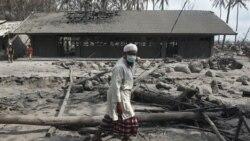 Seorang pria berjalan melewati bangunan sekolah di Cangkringan, Yogyakarta, yang terselimuti debu vulkanik dari letusan Gunung Merapi.