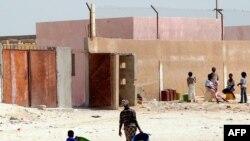 """Quelques personnes devant une ancienne école appelée par les locaux """"Guantanamito"""", transformée en 2006 en centre de détention pour immigrants clandestins dans la ville portuaire de Nouadhibou, Mauritanie, 9 octobre 2008."""