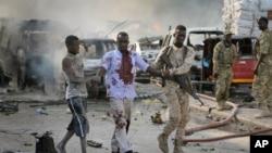 索马里首都摩加迪沙发生爆炸,图为一名军人搀扶一名受伤的平民。(2017年10月14日)
