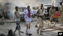 FILE - A Somali soldier helps a civilian who was wounded in a blast in the capital of Mogadishu, Oct. 14, 2017.