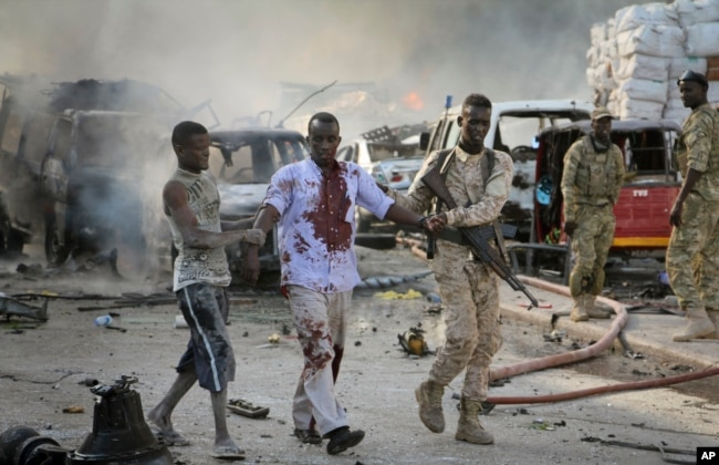 FILE - A Somali soldier helps a civilian who was wounded in a blast in the capital of Mogadishu, Somalia, Oct. 14, 2017.