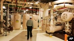 FILE - A worker walks past equipment in the turbine building at the Oyster Creek nuclear plant in Lacey Township, N.J., Feb. 25, 2010.