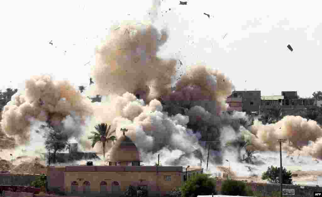Smoke rises after a house was blown up during a military operation by Egyptian security forces in Rafah near the border with southern Gaza Strip.